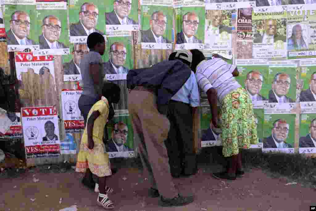 Residents of Epworth look through a hole in a fence covered in campaign posters, Harare, July 30, 2013.