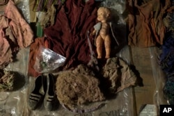 FILE - Clothing, earrings, and a doll that were found among the remains of over 100 Ixil Mayans exhumed from a mass grave, lay on display for hopeful identification by relatives in Santa Avelina, Guatemala, Nov. 29, 2017.
