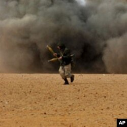 Libyan rebel fighters run for cover as shells explode nearby during a battle with forces loyal to leader Moammer Gadhafi, just few kilometers outside the oil town of Ras Lanuf, March 9, 2011