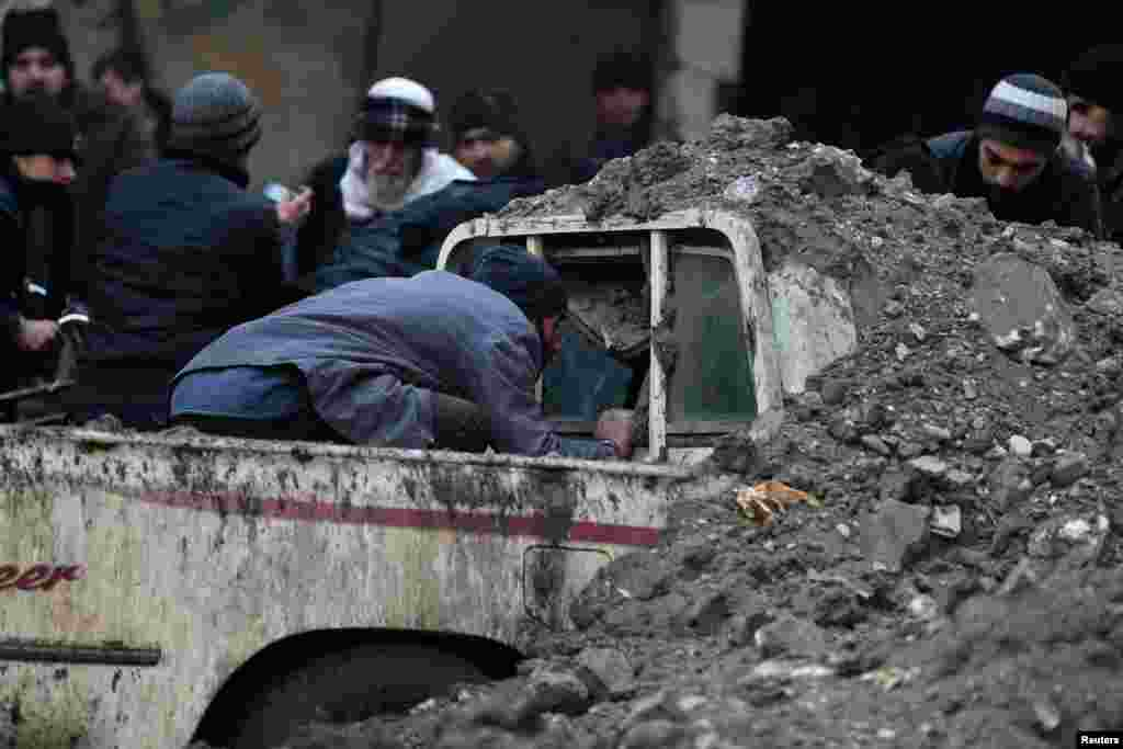 A man looks for survivors inside a pickup truck at a damaged site after what activists said was an airstrike by forces loyal to Syrian President Bashar al-Assad in Duma, Damascus.