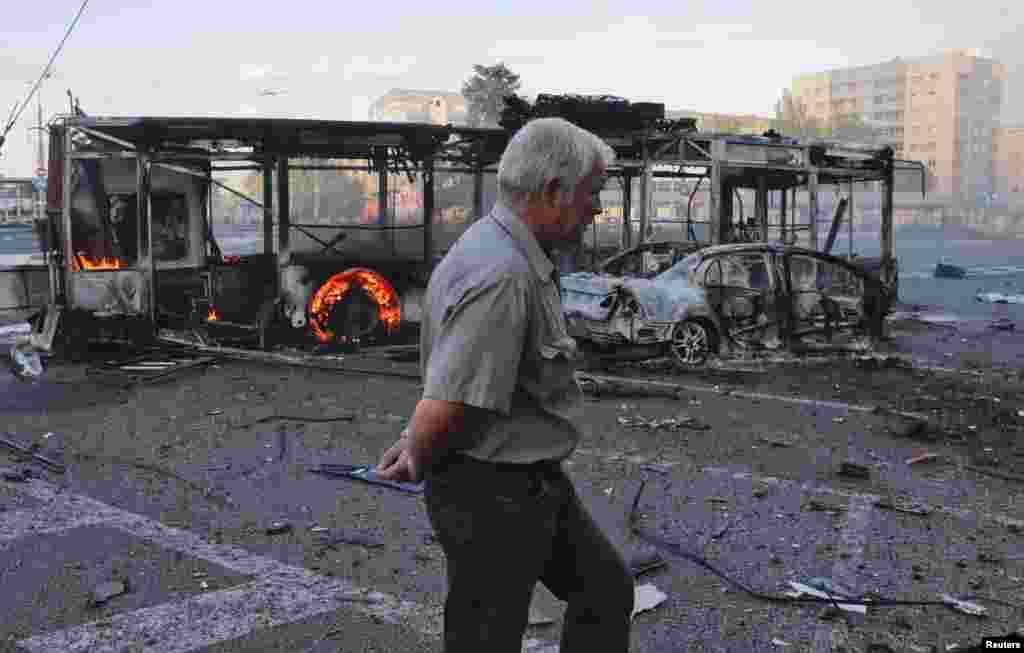 Một người đàn ông đi ngang qua những chiếc xe bị thiêu rụi tại một quảng trường gần nhà ga xe lửa sau đợt pháo kích hồi gần đây ở Donetsk, miền đông Ukraine.