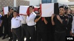 Para polisi Suriah membawa jenazah rekan mereka yang menjadi korban serangan di kota Jisr al-Shughour, Selasa (7/6).