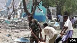 Tentara Somalia dan warga membawa korban tewas di lokasi ledakan bom mobil di Mogadishu (4/10).