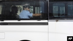 Sebuah mobil van polisi yang dilaporkan membawa beberapa wartawan Amerika yang ditangkap terlihat meninggalkan kantor penyidik di Manama, Bahrain (16/2).