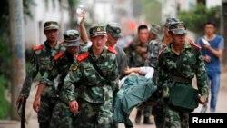 Polisi paramiliter China mengangkut korban tewas dan luka-luka di kota Ludian, provinsi Yunnan (3/8).