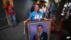 Một phụ nữ Tổng thống Hugo Chavez cầm bức ảnh của ông sau khi ông trở về nước, 18/2/13