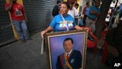 Una mujer sostiene una pintura del presidente Hugo Chávez: el tema de su juramentación también ha regresado a Venezuela.