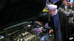 하산 로하니 이란 대통령이 1일 수도 테헤란에서 열린 국제 자동차 산업 박람회에 참석해 자동차 엔진을 들여다 보고 있다.