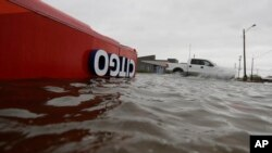 FILE - The roof of a gas station sits in flood waters in the wake of Hurricane Harvey in Aransas Pass, Texas, Aug. 26, 2017.