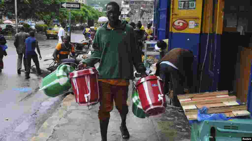 Un homme vent des seaux pour lavage des mains sur une rue de la ville de Monrovia, September 18, 2014. REUTERS/James Giahyue (LIBERIA - Tags: HEALTH SOCIETY DISASTER) - RTR46S4M