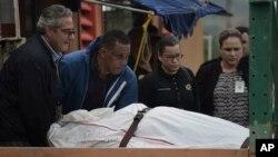 Trabajadores de la morgue en Puerto Rico retiran el cuerpo de un hombre muerto de un disparo, encontrado en San Juan. Enero 11, 2018.