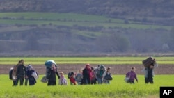 Migrants walk through a field near the northern Greek border station of Idomeni, Friday, March 4, 2016. More than 10,000 mostly Syrian and Iraqi refugees were stuck at the country's Idomeni border as Greek officials said that nearly 32,000 migrants were stranded in the country after drastically reduce of number of transiting migrants.(AP Photo/Vadim Ghirda)