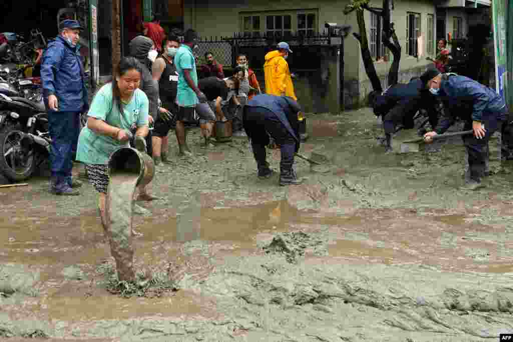 Residents and rescue workers clean an area which was flooded after Bishnumati river overflowed following heavy monsoon rains in Kathmandu, Nepal.