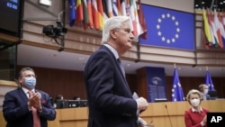 Head of the Task Force for Relations with the UK Michel Barnier, center, and European Commission President Ursula von der Leyen, right, attend a debate on the EU-UK trade and cooperation agreement at the European Parliament in Brussels, April 27, 2021.