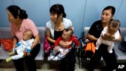 在为农民工提供母婴检查的北京朝阳区十八里店乡医院,中国妇女抱着孩子等着看医生。(2007年9月5日资料照)