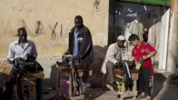 Migrant workers repairing clothes in the street in Benghazi, Libya
