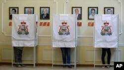 Warga memberikan suaranya dalam pemilihan parlemen di sebuah TPS di Smolensk, Rusia barat (18/9). (AP/Sergei Grits)