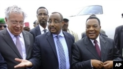 U.N.'s special representative to Somalia Augustine Mahiga (r) is greeted by Somali PM Abdiweli Mohamed Ali (center) as he arrives at the airport in Mogadishu, Somalia, January 24, 2012.