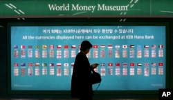 FILE - A woman walks by a board displaying various banknotes issued in the world at a subway station in Seoul, South Korea, Oct. 19, 2017. According to estimates, Chinese sanctions over Seoul's deployment of the THAAD missile defense system might have cost South Korea $7.5 billion in the first 10 months of this year.