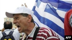 Протестувальник перед будинком парламенту в Афінах