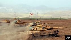 FILE - Turkish army tanks move during exercises in Silopi, near the Habur border gate with Iraq, southeastern Turkey, Sept. 25, 2017. (DHA-Depo Photos via AP)
