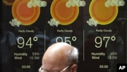這名男子7月21日在紐約的時報廣場的天氣預告牌前走過