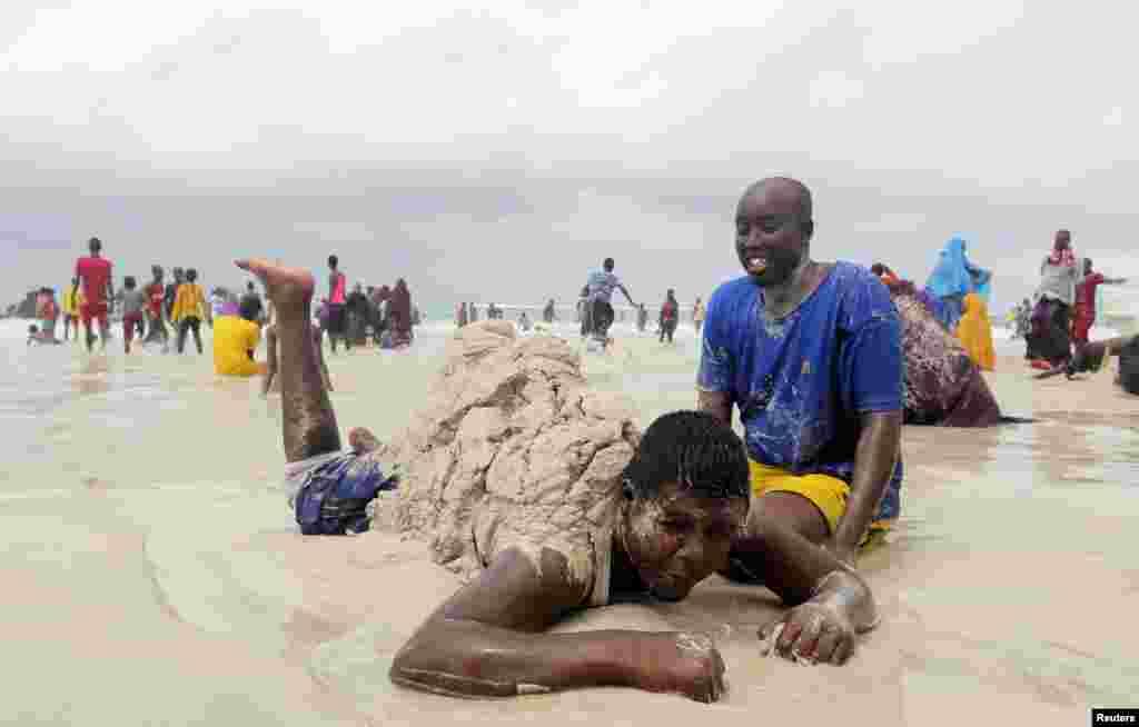 شہری ساحل سمندر پر ریت سے کھیل رہے ہیں۔