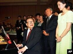 1998年7月3日,中国主席江泽民在哈萨克斯坦的阿拉木图的招待会上弹钢琴,用中文演唱哈萨克歌曲,哈萨克总统(右二)在旁边。