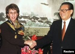 资料照片:美国贸易代表巴尔舍夫斯基与中国领导人江泽民在北京举行的WTO签字仪式上握手。(1999年11月15日)