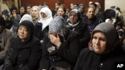 Women react inside the Kurdish cultural center in Paris, January 10, 2013.