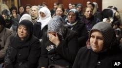 Women react inside the Kurdish cultural center in Paris, January 10, 2013.