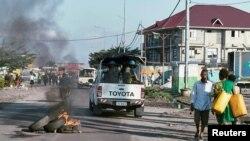 지난 4월 반정부 시위가 발생한 콩고민주공화국 수도 킨샤사 거리에서 타이어가 불에 타고 있는 가운데, 유엔 평화유지군 차량이 지나고 있다.