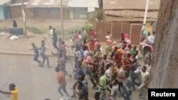 Demonstrators run along a street in Asella, Oromiya Province, Ethiopia Feb. 13, 2018, in this still image taken from a social media video. (TWITTER/@WAGUWAGU91)