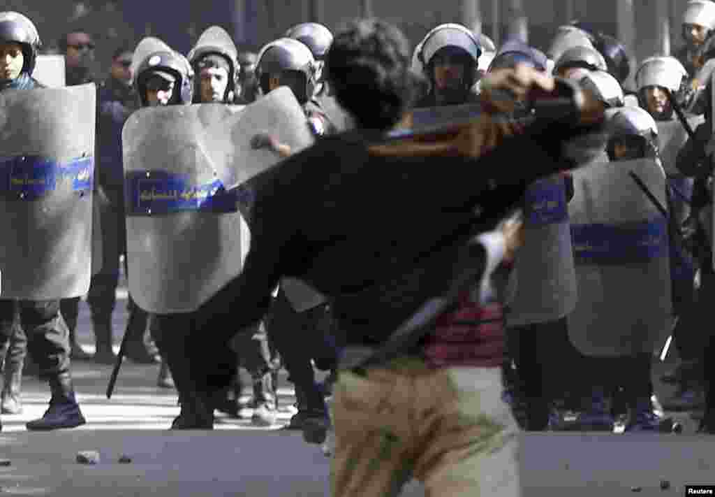 A protester opposing Egyptian President Mohamed Morsi throws a stone at riot policemen during the funeral of activists Mohamed al-Gendy and Amr Saad in Cairo.