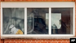 Medical practitioners wearing protective clothing are seen through a window inside an isolated ward on the sixth floor of the the Carlos III hospital in Madrid, Spain on October10, 2014.