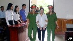 Nhà hoạt động Trần Thị Xuân bị dẫn vào phòng xử án hôm 12/4 tại Hà Tĩnh.