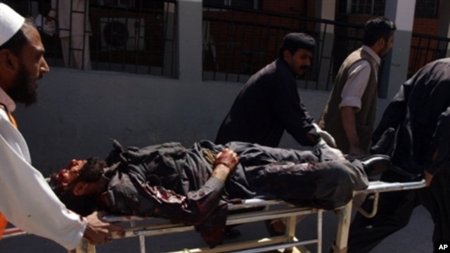 Pakistani volunteers push a stretcher carrying an injured paramilitary soldier at a hospital after a huge suicide bomb attack on the US consulate in Peshawar on 5 Apr 2010