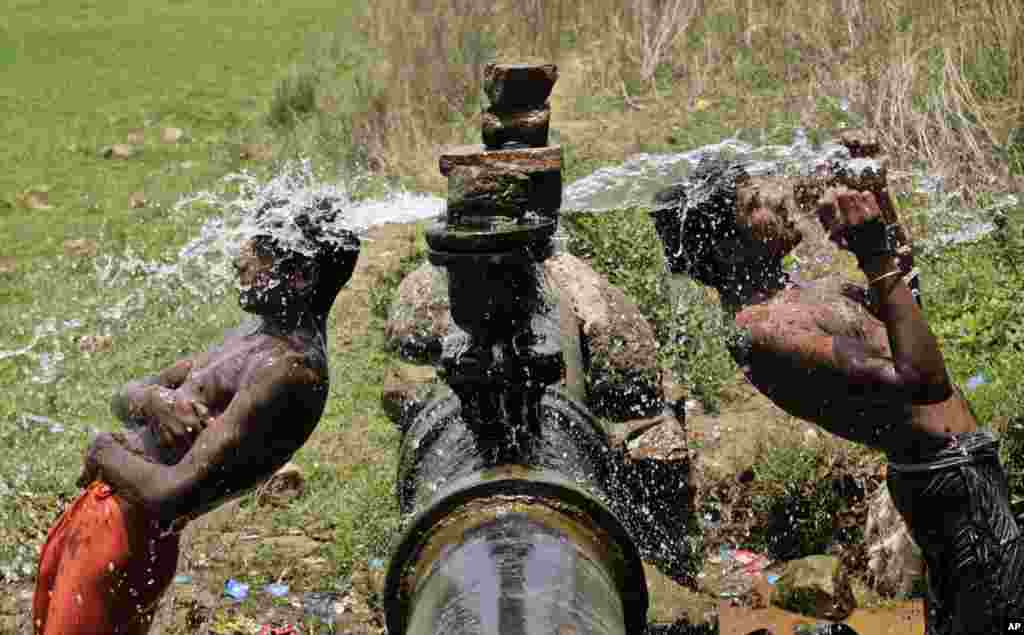 Slum dwellers bathe in water gushing out of a leakage from a pipe on the outskirts of Bhubaneswar, India.