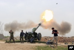 FILE - Iraqi security forces fire at Islamic State positions from villages south of Mosul, Iraq, March 26, 2016.