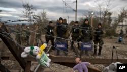 在希腊-马其顿边界上,移民吧玩具放到铁丝网上,对面的马其顿警察(2015年11月29日)
