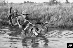 FILE - A South Vietnamese soldier holds his personal belongings in a plastic bag between his teeth as his unit crosses a muddy Mekong Delta stream in Vietnam near the Cambodian border, March 11, 1972. His unit was charged with stemming Communist infiltrat