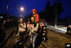 People walk on the railway tracks as they cross the borders from the northern Greek village of Idomeni to southern Macedonia, Sept. 21, 2015.