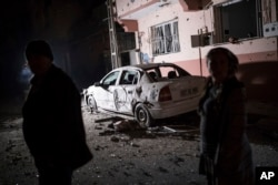 People look at the damage caused by a rocket fired by suspected Syrian Kurdish fighters from Syria, across the border, into the town of Kilis, Turkey, early Jan. 21, 2018. According to the local governor four rockets struck the town, hitting two houses and an office, injuring one person.