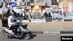 A poster depicting Sunni politician Ashraf Rifi (C) is seen among posters of Lebanese candidates that were running in Tripoli's municipal and mayoral elections, Lebanon, May 30, 2016.