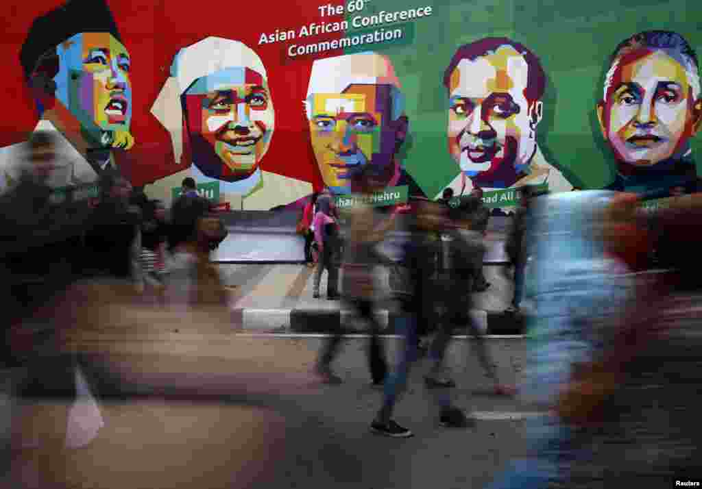 People walk in front a poster of prominent attendees of the 1955 Asian-African Conference on Asia Afrika street in Bandung, Indonesia, April 24, 2015. Leaders of Asian and African nations attended a commemoration ceremony on Friday marking 60 years since the commemoration of the Asian-African Conference.