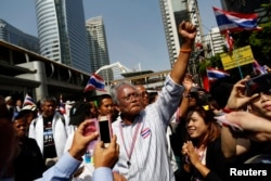 FILE - Protest leader Suthep Thaugsuban greets the crowd as he leads anti-government protesters marching through Bangkok's financial district, Jan. 21, 2014.