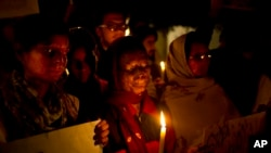 India Acid Attack: FILE - In this Dec. 16, 2014 file photo, acid attack survivors participate in a candlelit vigil protesting violence against women as they mark the second anniversary of the deadly gang rape of a student on a bus, in New Delhi, India.