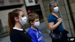 A family wearing face mask to protect of the coronavirus go for a walk, in Pamplona, northern Spain, Sunday, April 27, 2020. On Sunday, children under 14 years old will be allowed to take walks with a parent for up to one hour and within one…