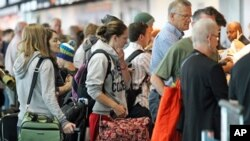 People wait in line at the security checkpoint at the Portland International Airport, July 3, 2012, in Portland, Oregon.