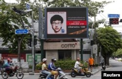FILE - People ride their motorcycles past a digital billboard showing a sketch of the main suspect in Monday's attack on Erawan shrine, in Bangkok, Thailand, August 23, 2015.